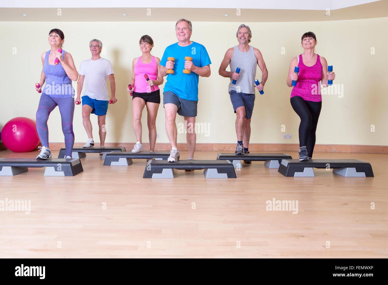 Altos pasos clase con pesas en el gimnasio Foto de stock