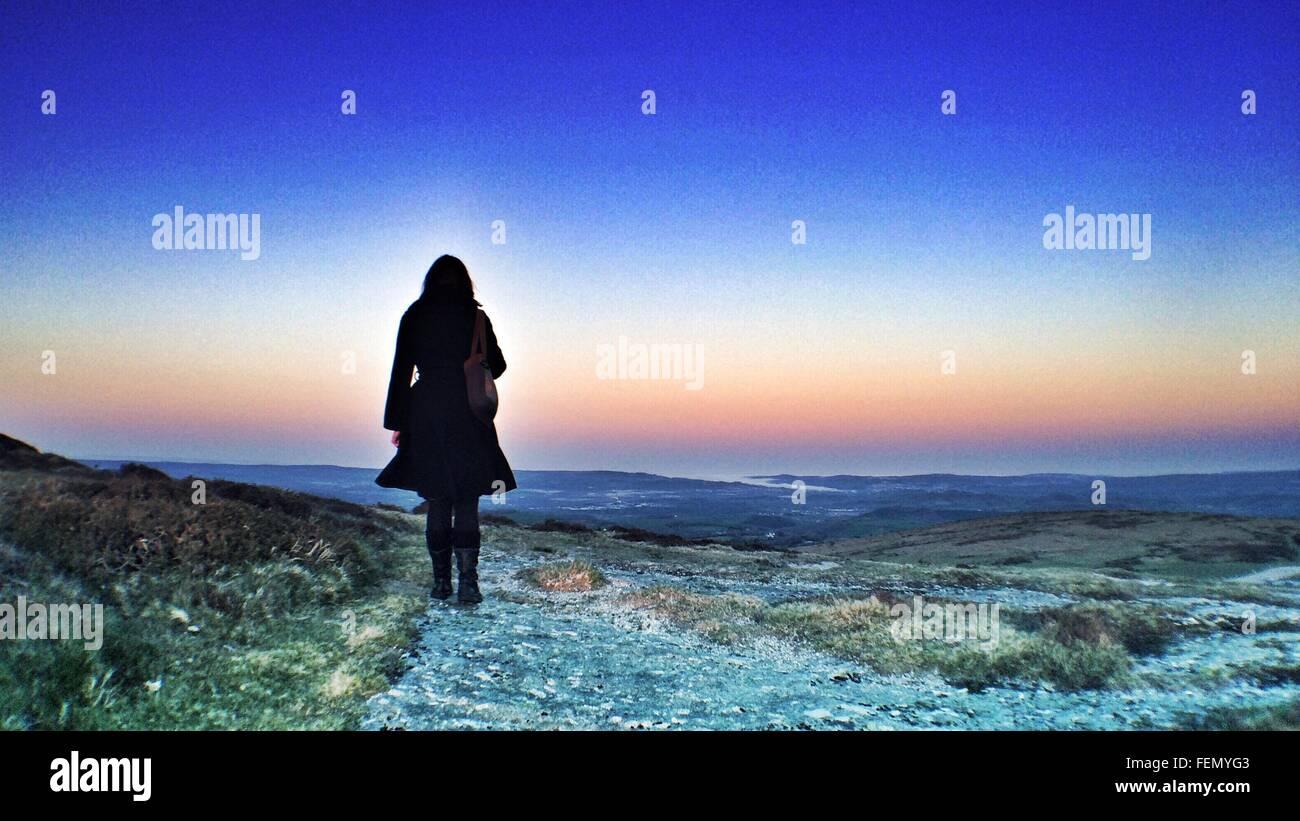 Vista trasera de la Mujer de pie contra el cielo espectacular Imagen De Stock