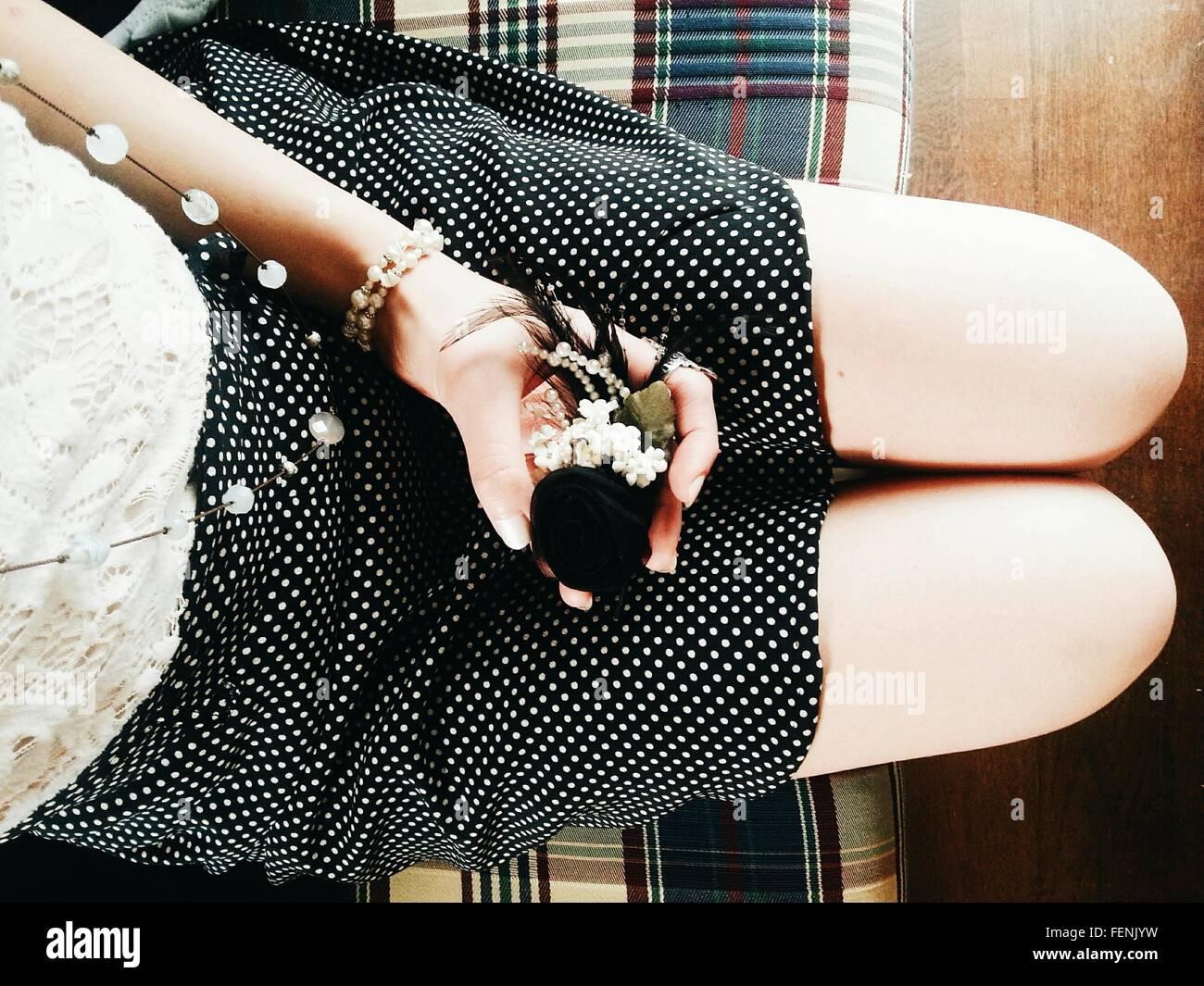 La mitad del torso de mujer sosteniendo ornamento, mientras están sentados en un sofá Imagen De Stock