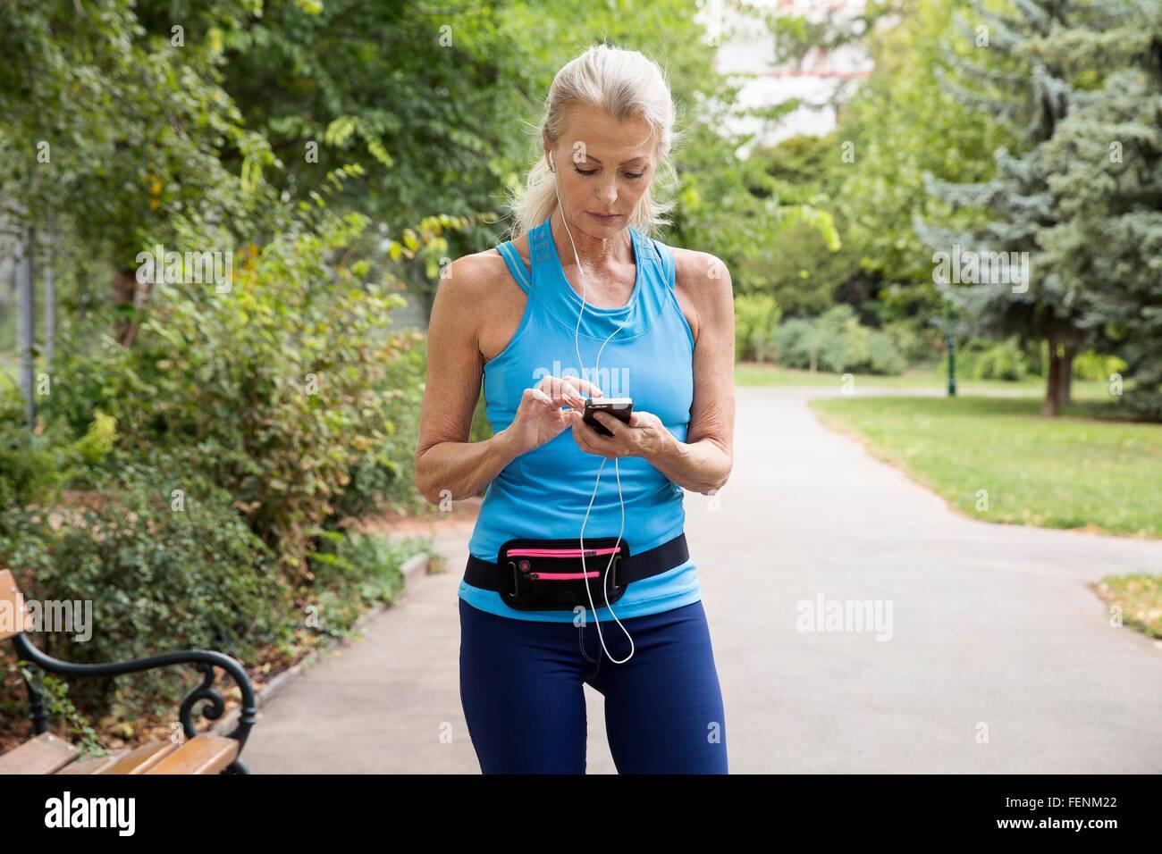Mujer madura, elegir la música del smartphone, mientras que la capacitación en park Imagen De Stock