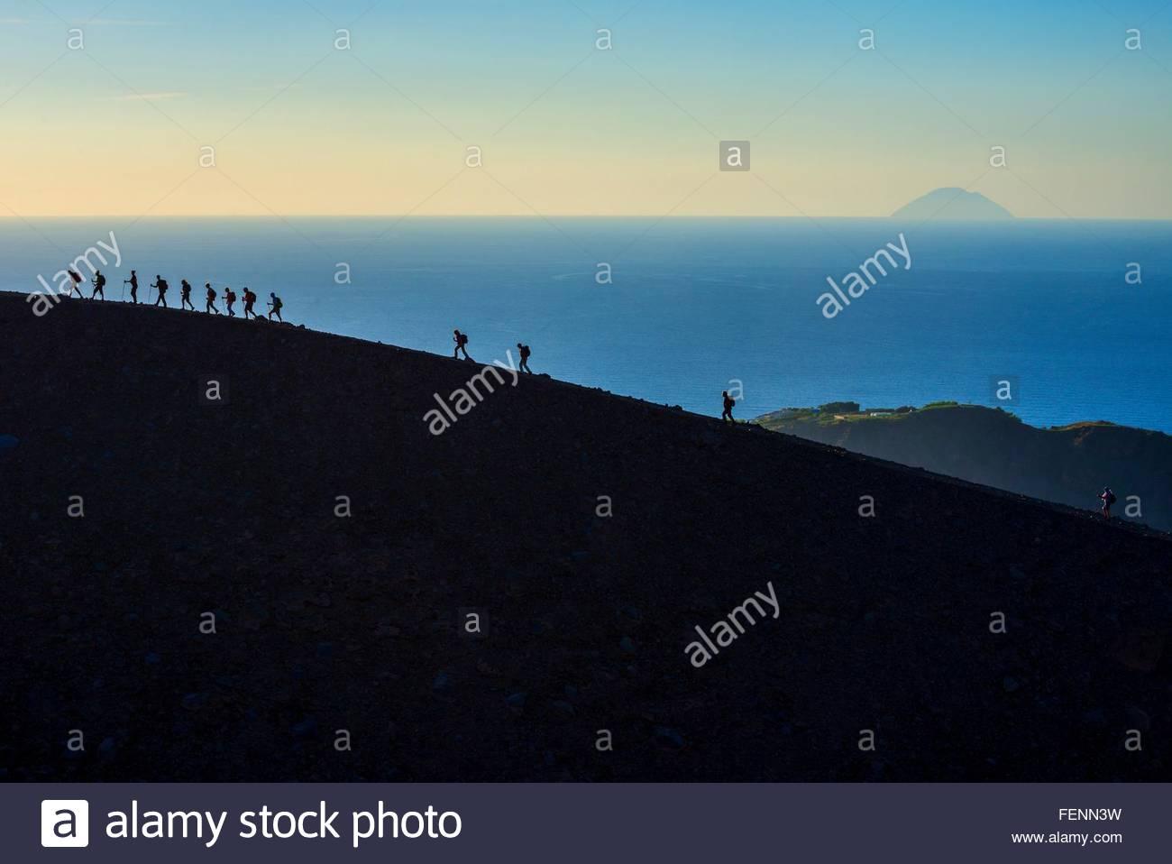 Gran grupo de siluetas de los turistas que caminan por rim en Gran Cratere, Isla de Vulcano, las Islas Eolias, en Imagen De Stock