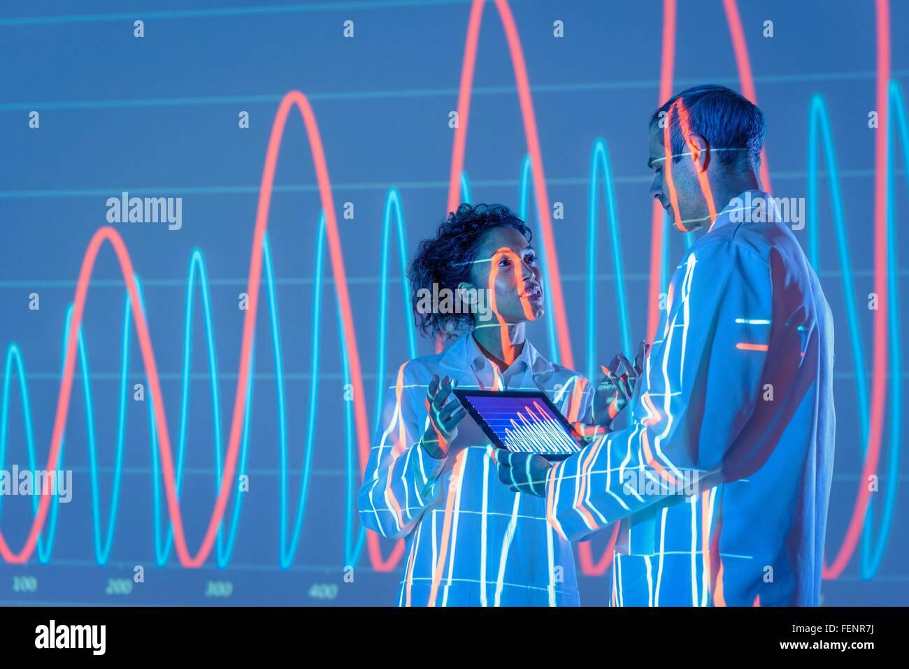 Los científicos en el debate con proyección de datos gráfica Imagen De Stock