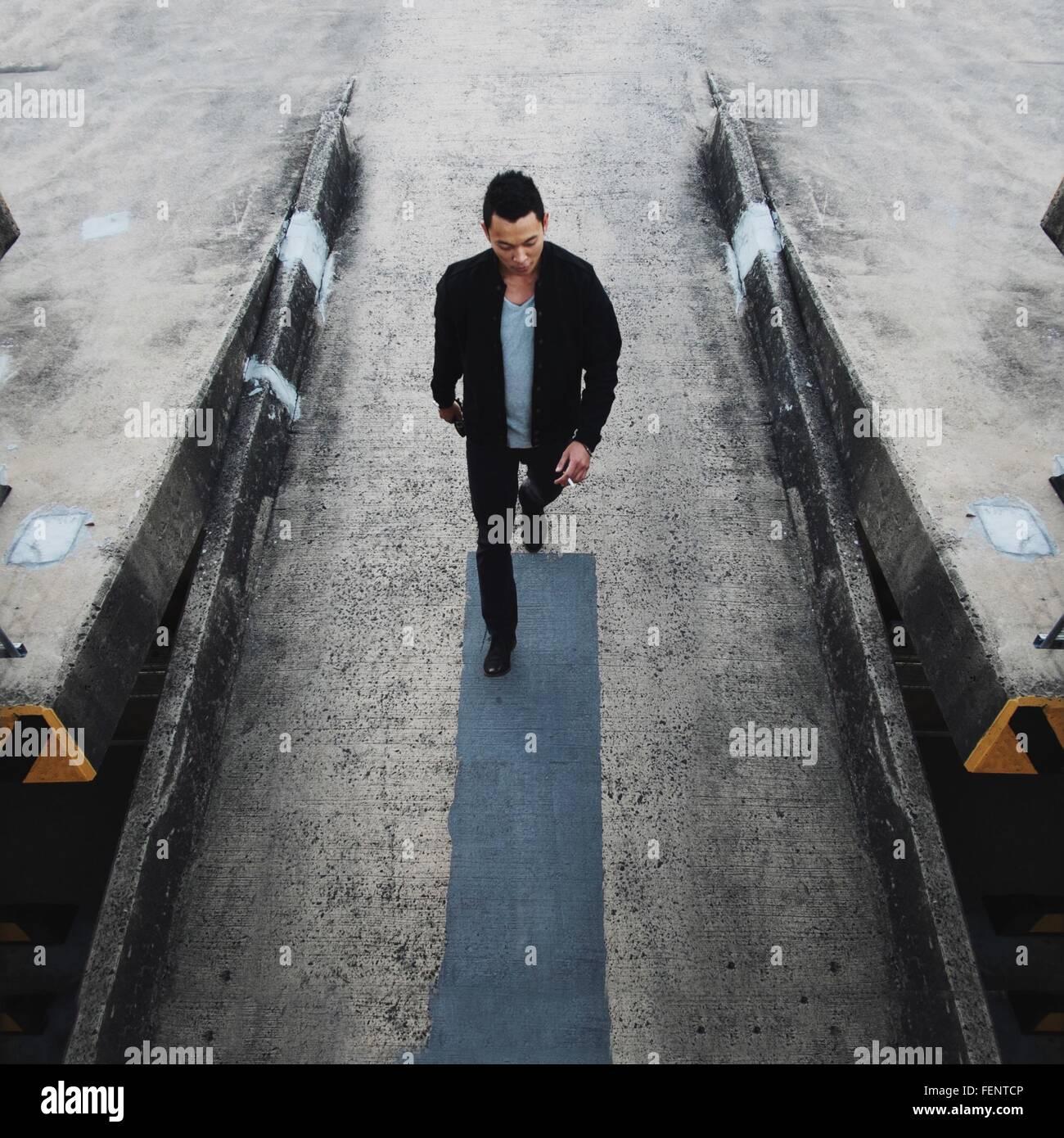 Un alto ángulo de visualización del guapo joven andando calle abajo Foto de stock