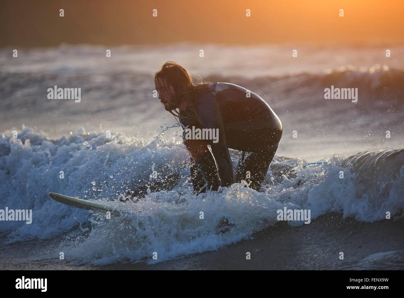 Macho joven surfista surf en las olas del océano, Devon, Inglaterra, Reino Unido. Imagen De Stock