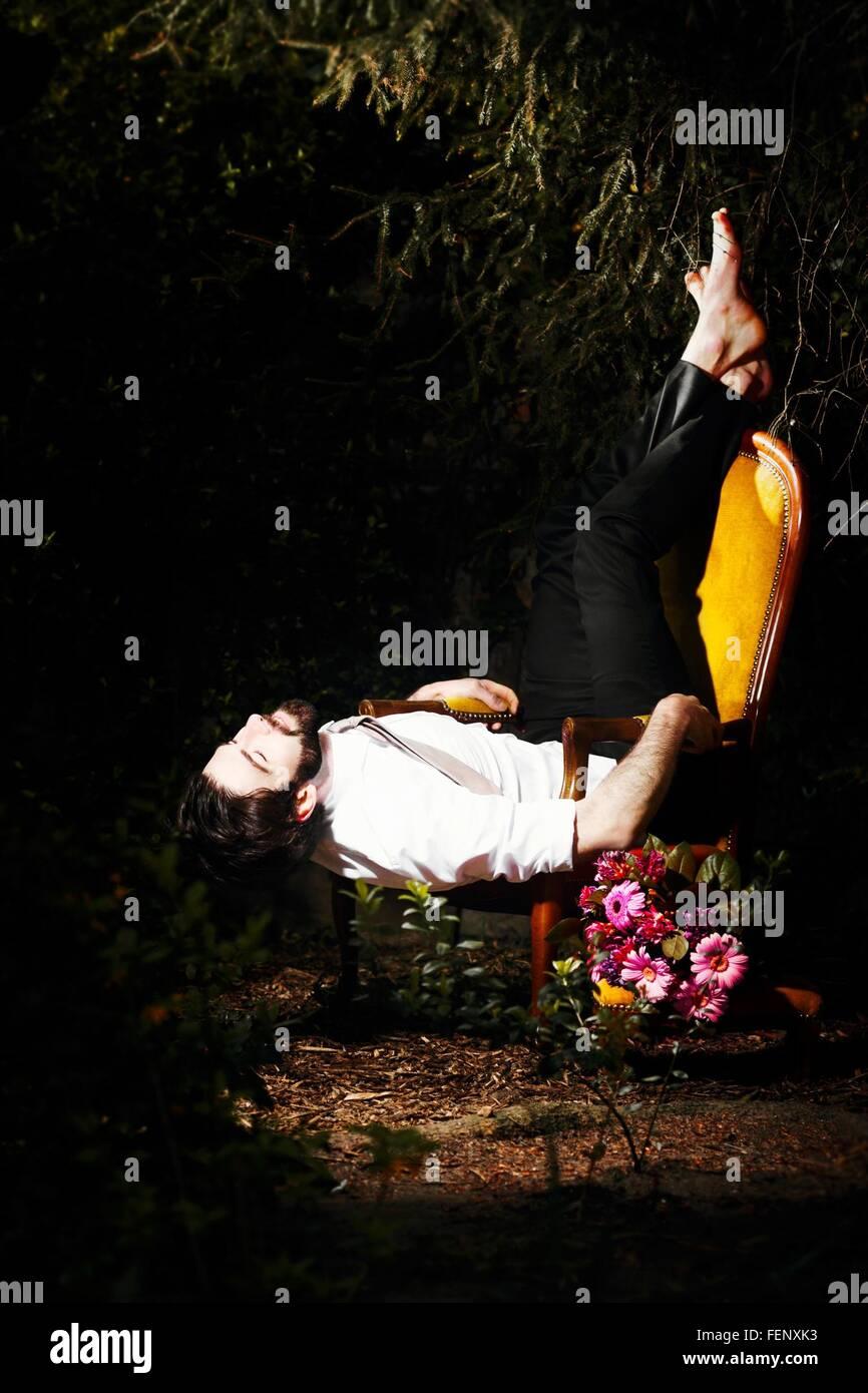 Hombre descansando en una silla en el jardín Foto de stock