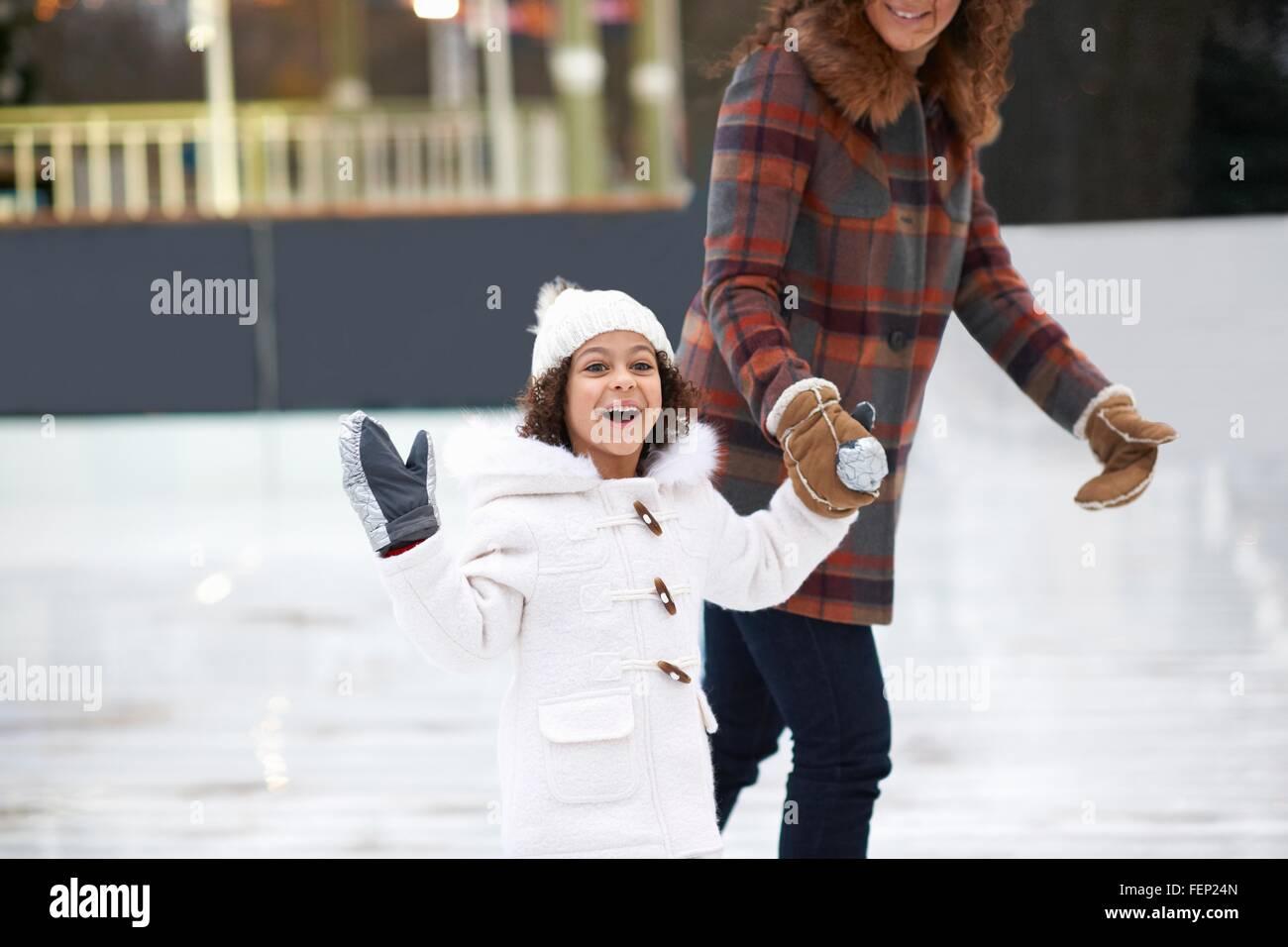 Chica a patinar sobre hielo con las manos de la madre, mirando a la cámara sonriendo Imagen De Stock