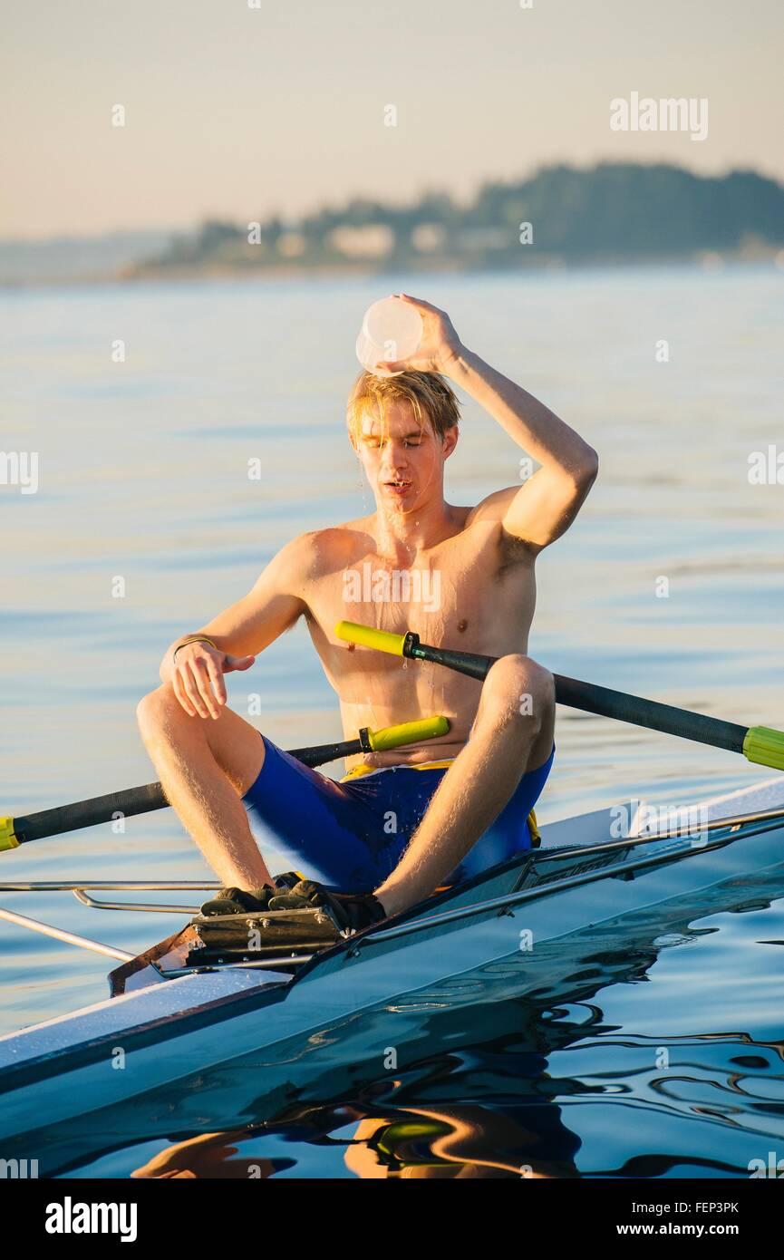 Adolescente en barco sculling, verter agua sobre la cabeza para enfriar él hacia abajo Imagen De Stock