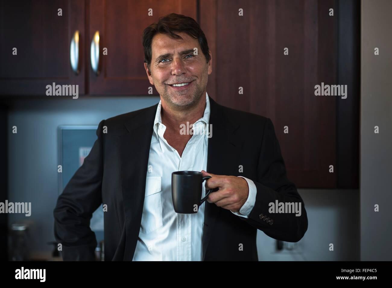 Hombre maduro, vistiendo camisa y traje chaqueta sosteniendo la taza de café mirando a la cámara sonriendo Foto de stock