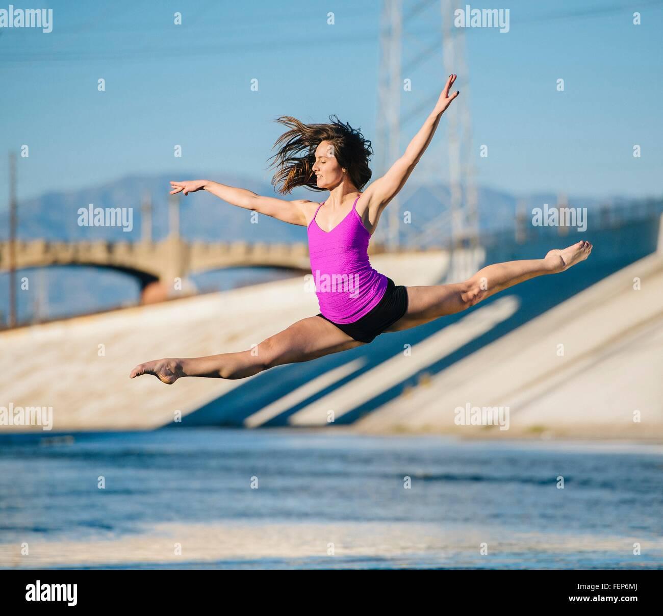 Bailarina en medio del aire, brazos levantados haciendo las divisiones, Los Ángeles, California, Estados Unidos. Imagen De Stock