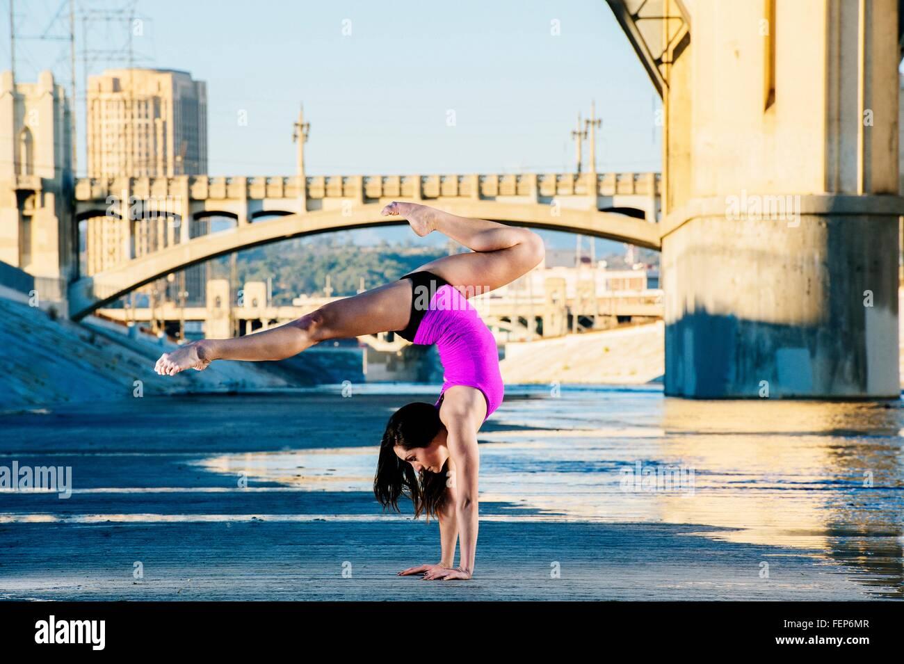 Vista lateral del bailarín haciendo pino, piernas abiertas, Los Ángeles, California, Estados Unidos. Imagen De Stock