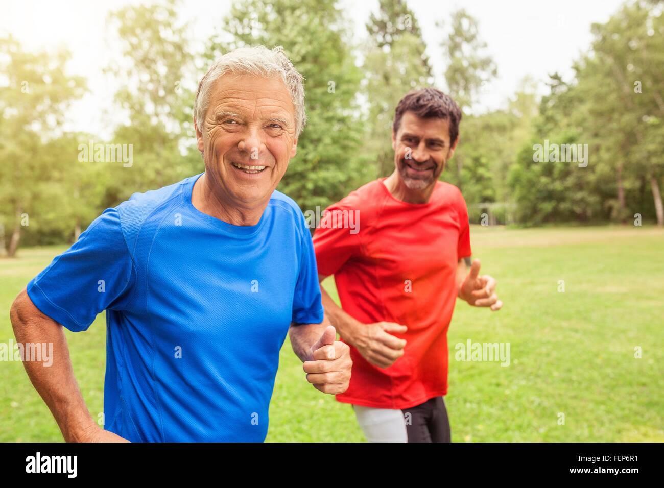 Dos hombres corriendo en exteriores, sonriendo Foto de stock