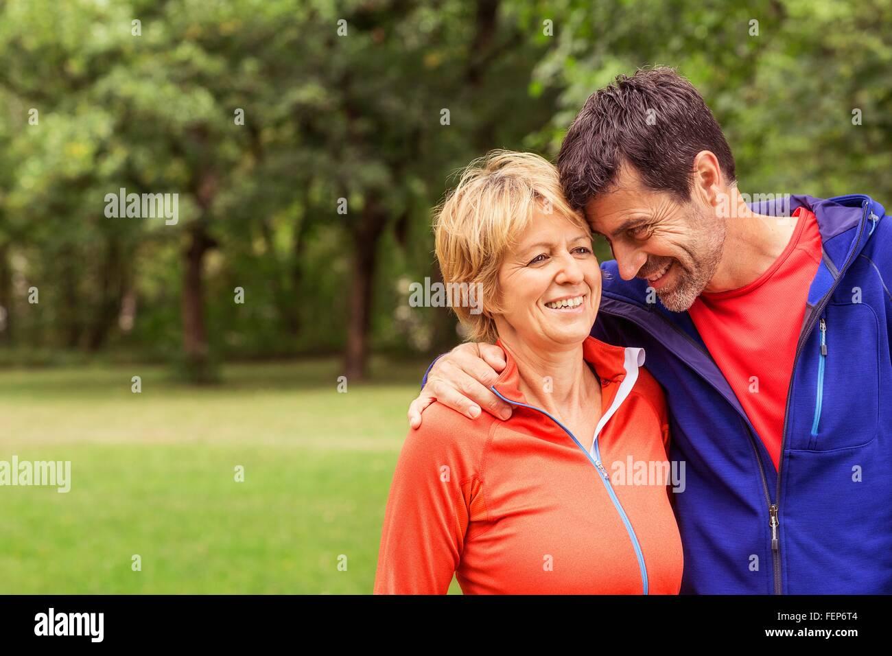 Par llevaba ropa deportiva al aire libre, un abrazo, sonriente Imagen De Stock