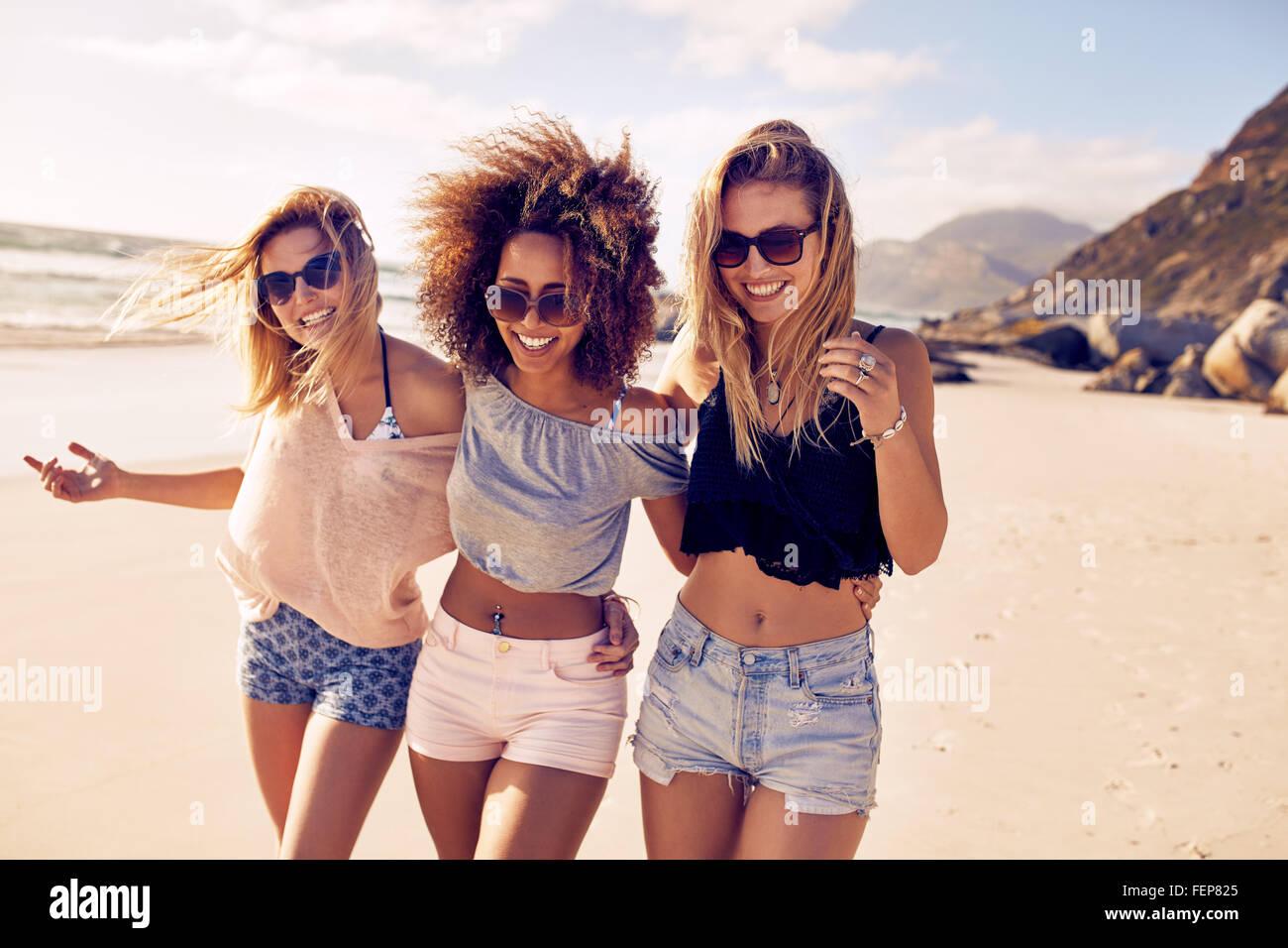 Retrato de tres amigas jóvenes caminando por la orilla del mar mirando a la cámara riendo. Las mujeres Imagen De Stock