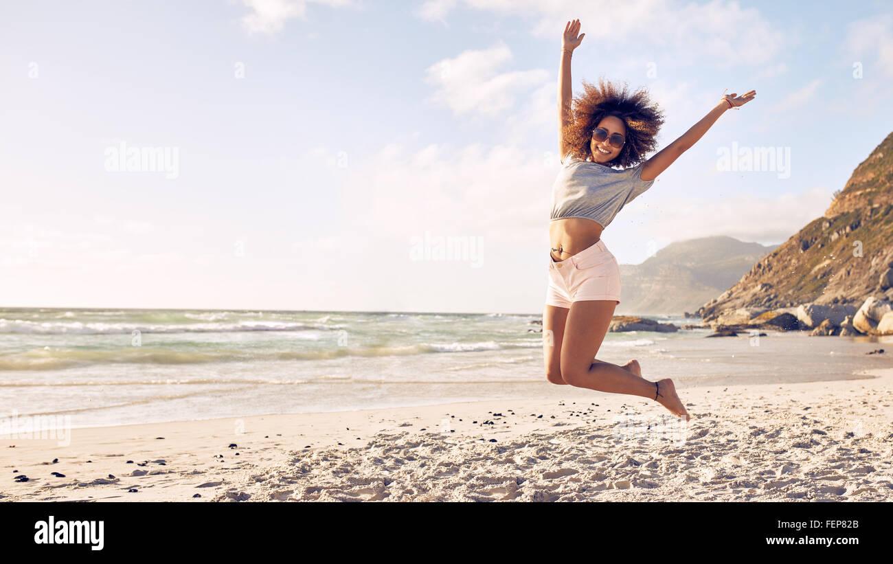 Retrato de joven bella saltar en el aire en la playa. Hembra africana disfrutando de un día de verano en la Imagen De Stock