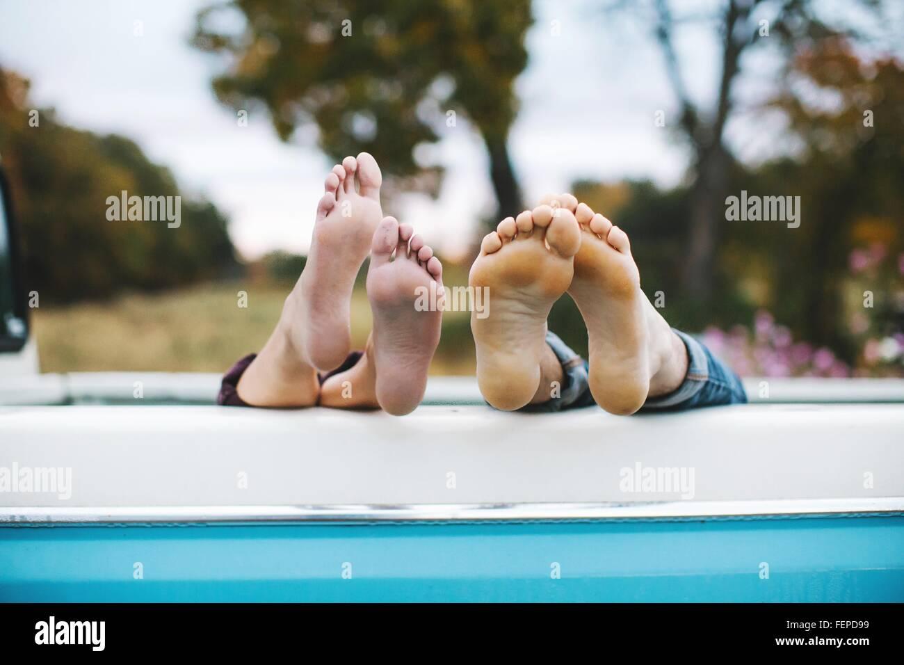 Pareja joven tumbado en la parte trasera de la carretilla, los pies descalzos en el borde de la carretilla, se centran Imagen De Stock