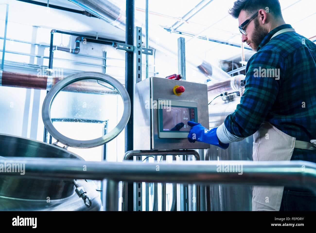Joven en la cervecería vistiendo delantal y guantes protectores de pantalla táctil utilizando equipos Imagen De Stock