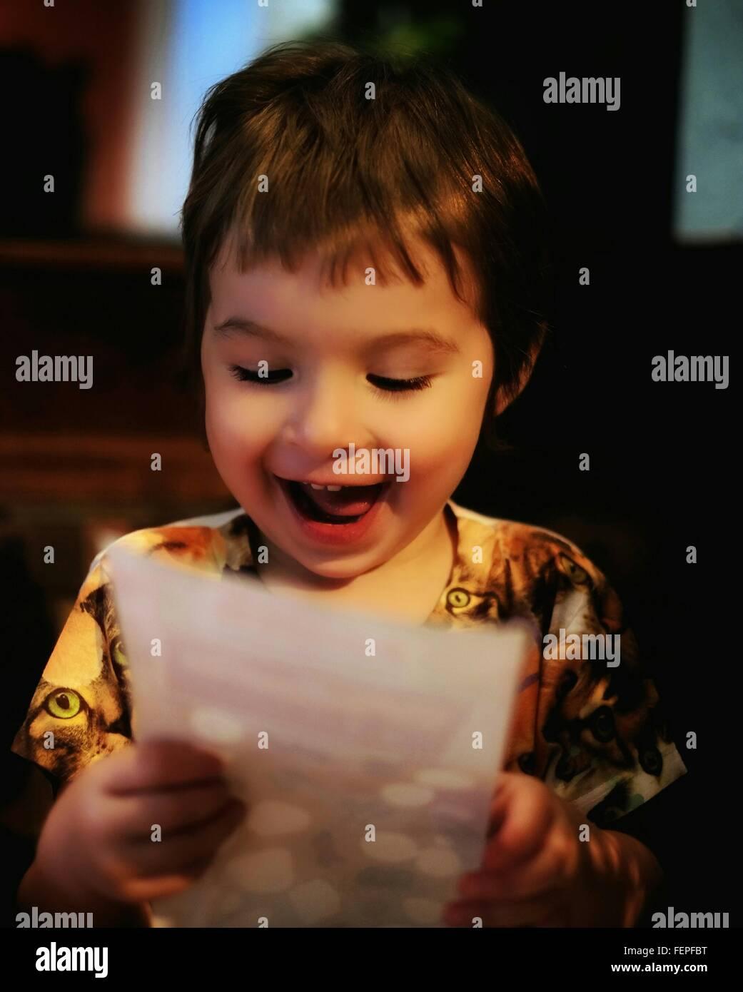 Niña feliz Lectura Carta en casa Imagen De Stock