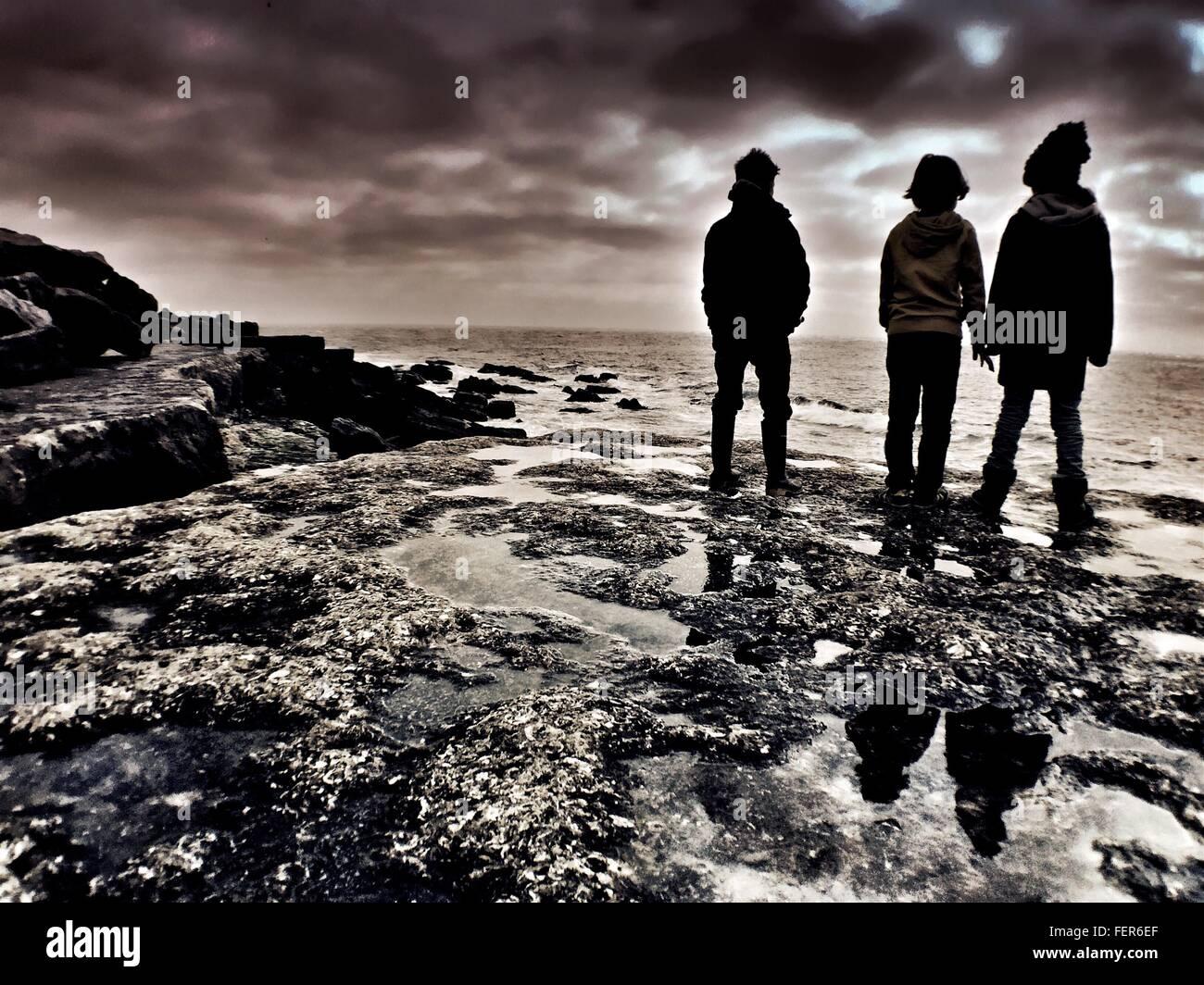Raro ver la silueta de los muchachos en la playa permanente contra el cielo nublado Imagen De Stock