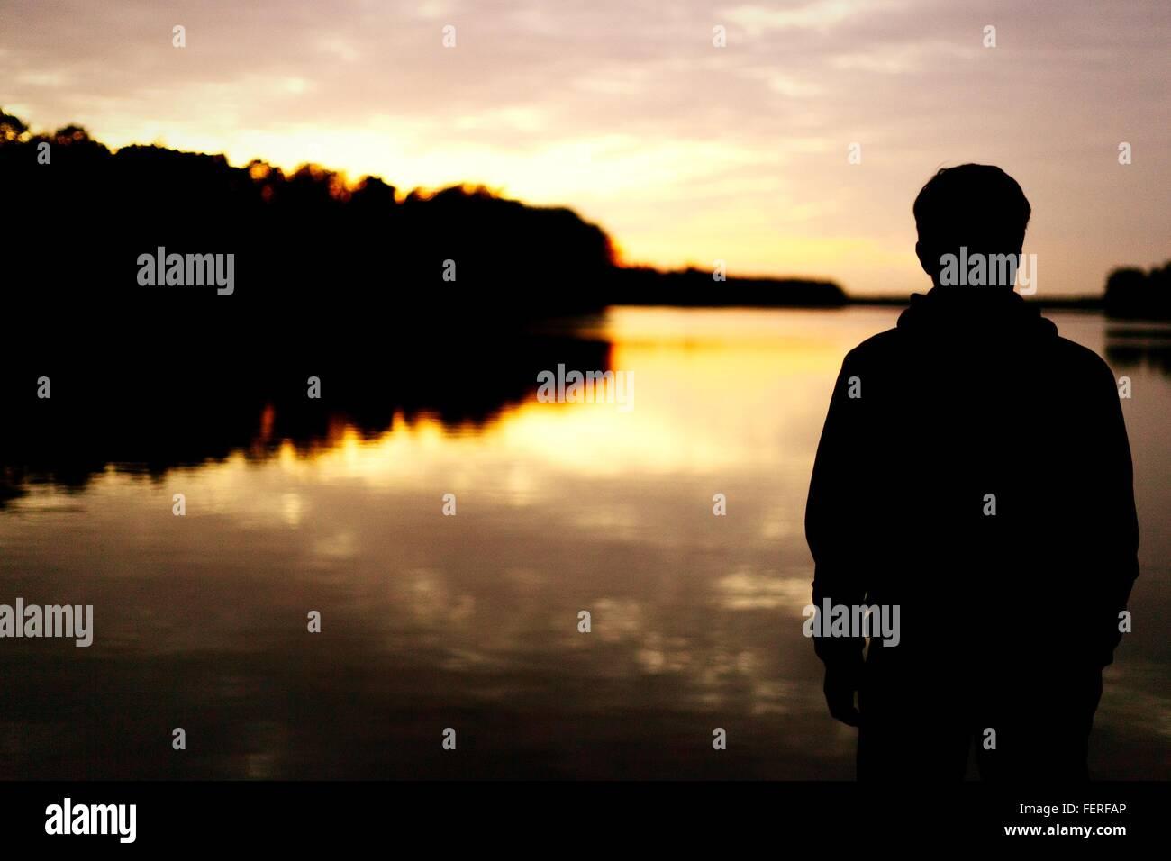 Vista trasera de la Silueta Hombre de pie en frente del lago al atardecer. Foto de stock