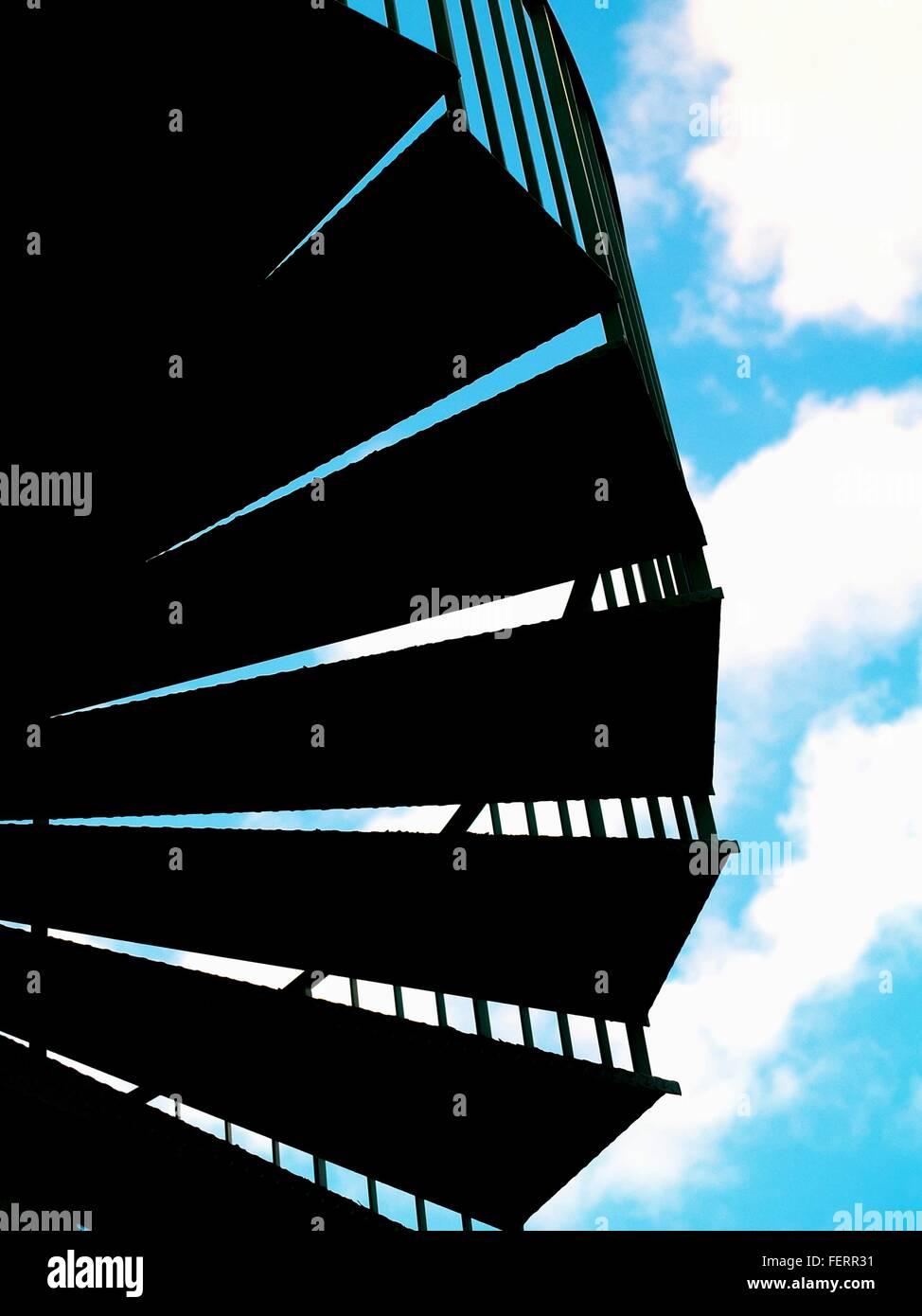 Ángulo de visión baja de silueta pasos contra el cielo nublado Imagen De Stock