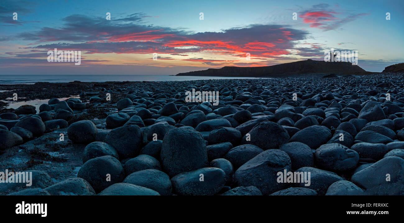 Una vista al amanecer del castillo de Dunstanburgh tomada de la WHIN Sill rocas al Norte Imagen De Stock