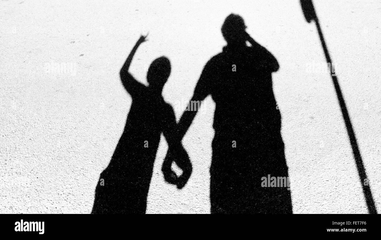 Sombra de padre e hijo cogidos de la mano en la calle Imagen De Stock
