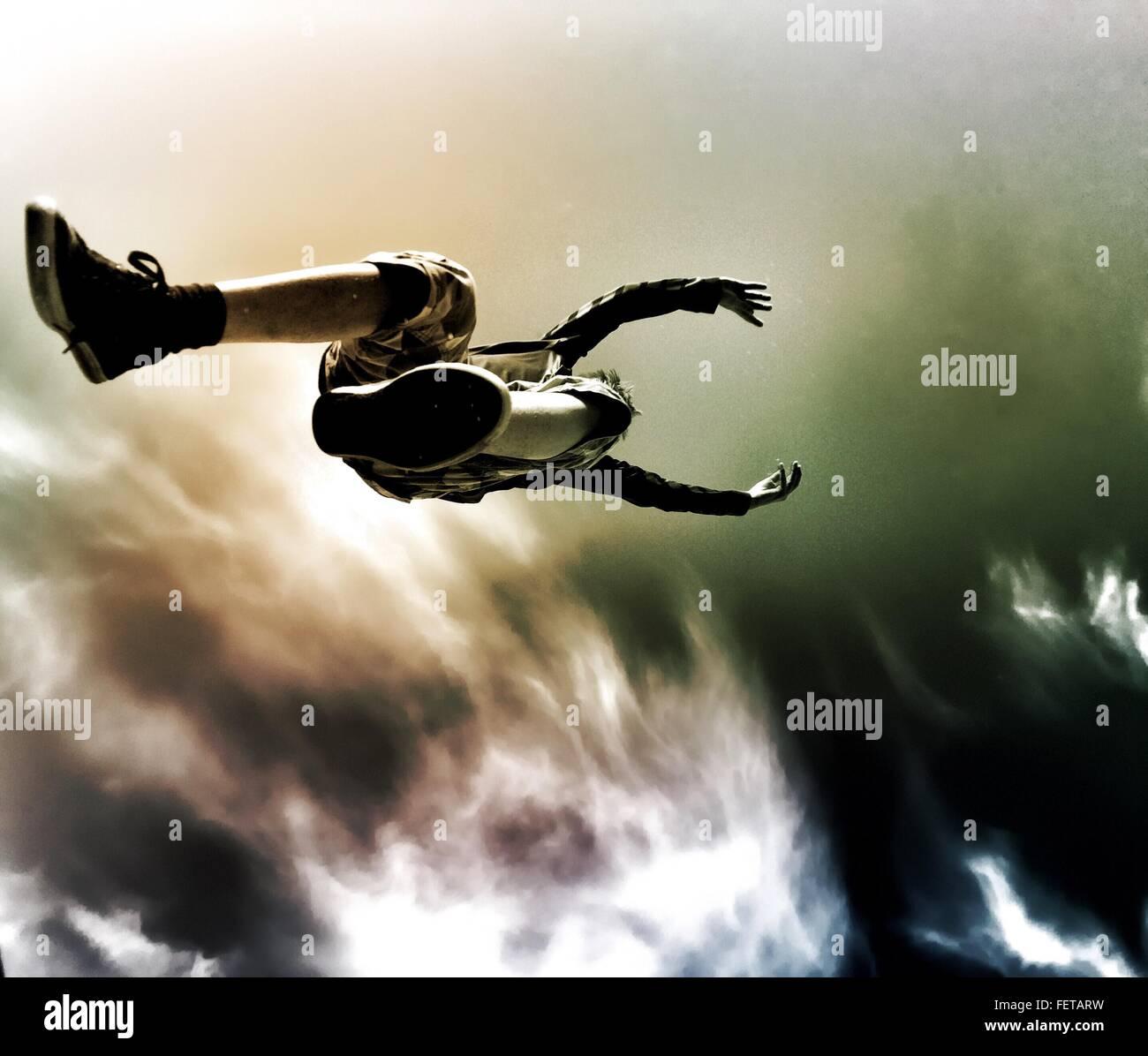 Directamente debajo de la foto de Boy saltando contra el cielo nublado Imagen De Stock