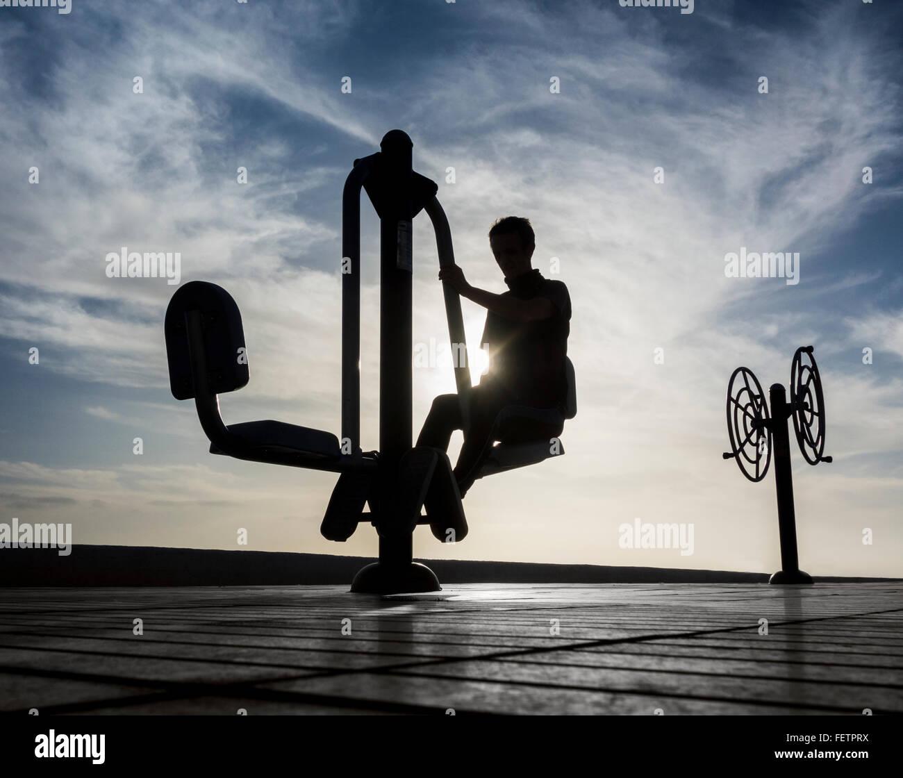 Hombre en máquina de ejercicio con vistas al mar al amanecer. Imagen De Stock