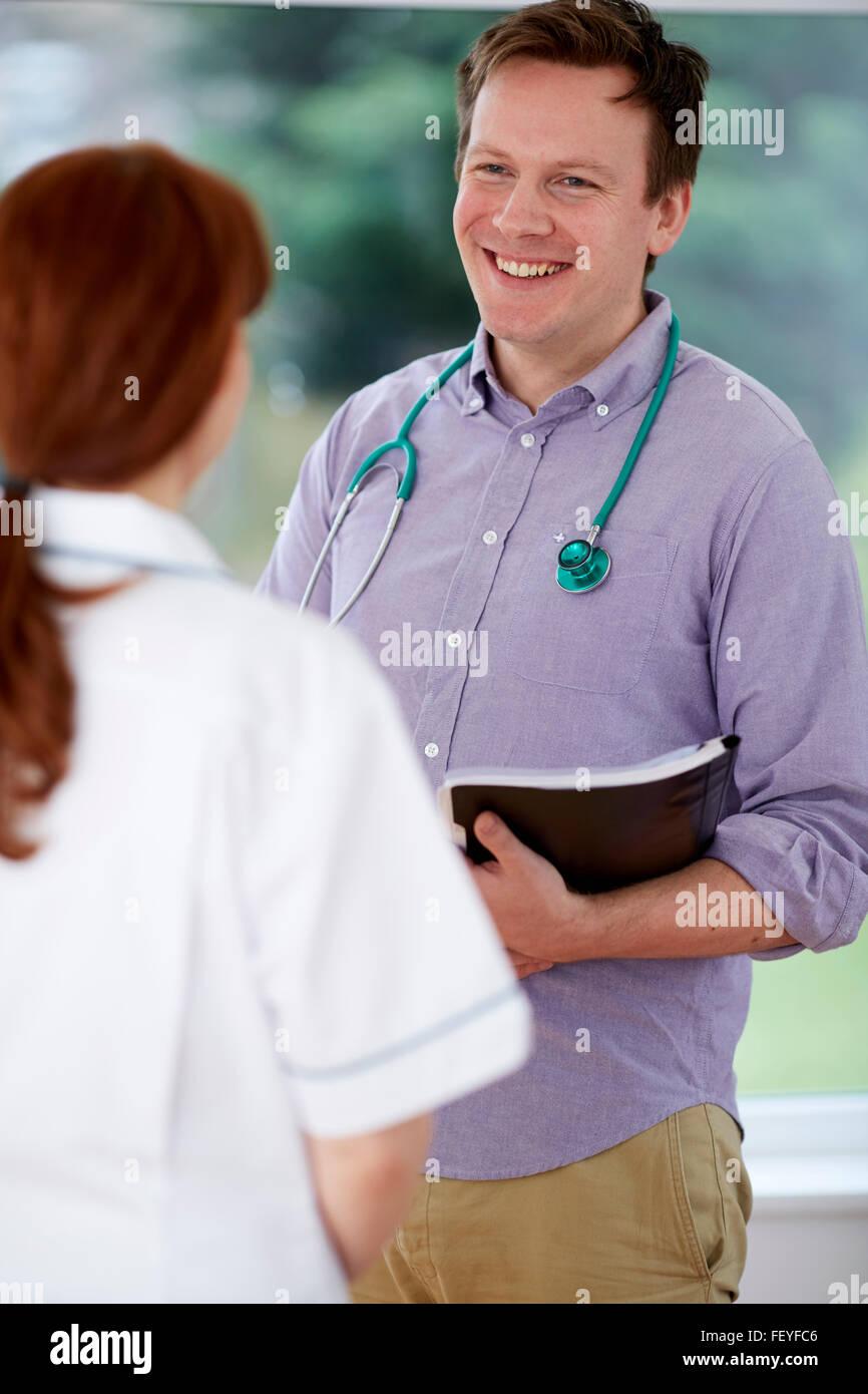 Un médico y una enfermera discutiendo notas Imagen De Stock