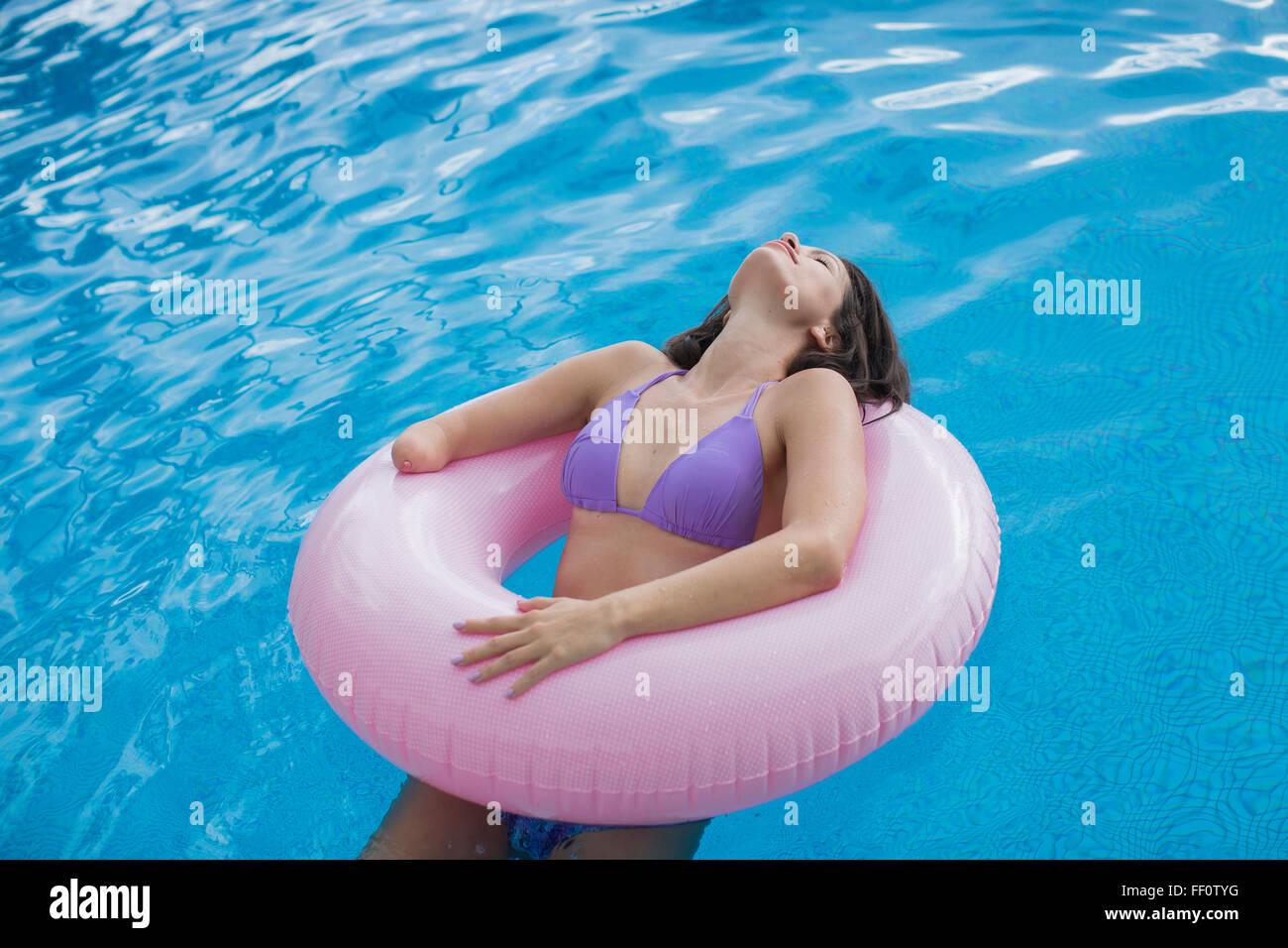 Mujer de raza mixta amputados nadar en piscina Foto de stock