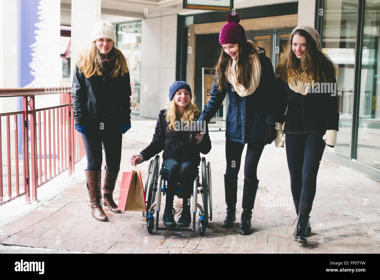 Las niñas caminar y usar silla de ruedas sobre la acera Foto de stock