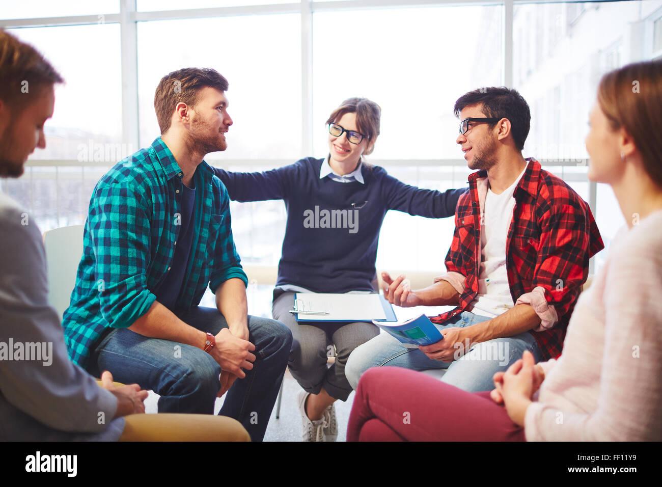 Feliz joven apoyando a sus amigos la decisión en el curso de terapia psicológica Imagen De Stock