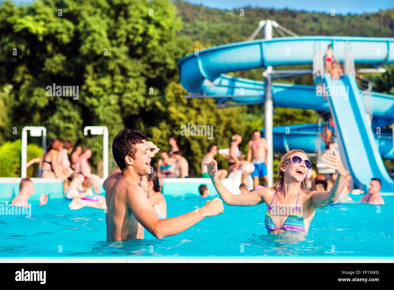 Pareja joven en piscina en día soleado. Tobogán de agua. Imagen De Stock