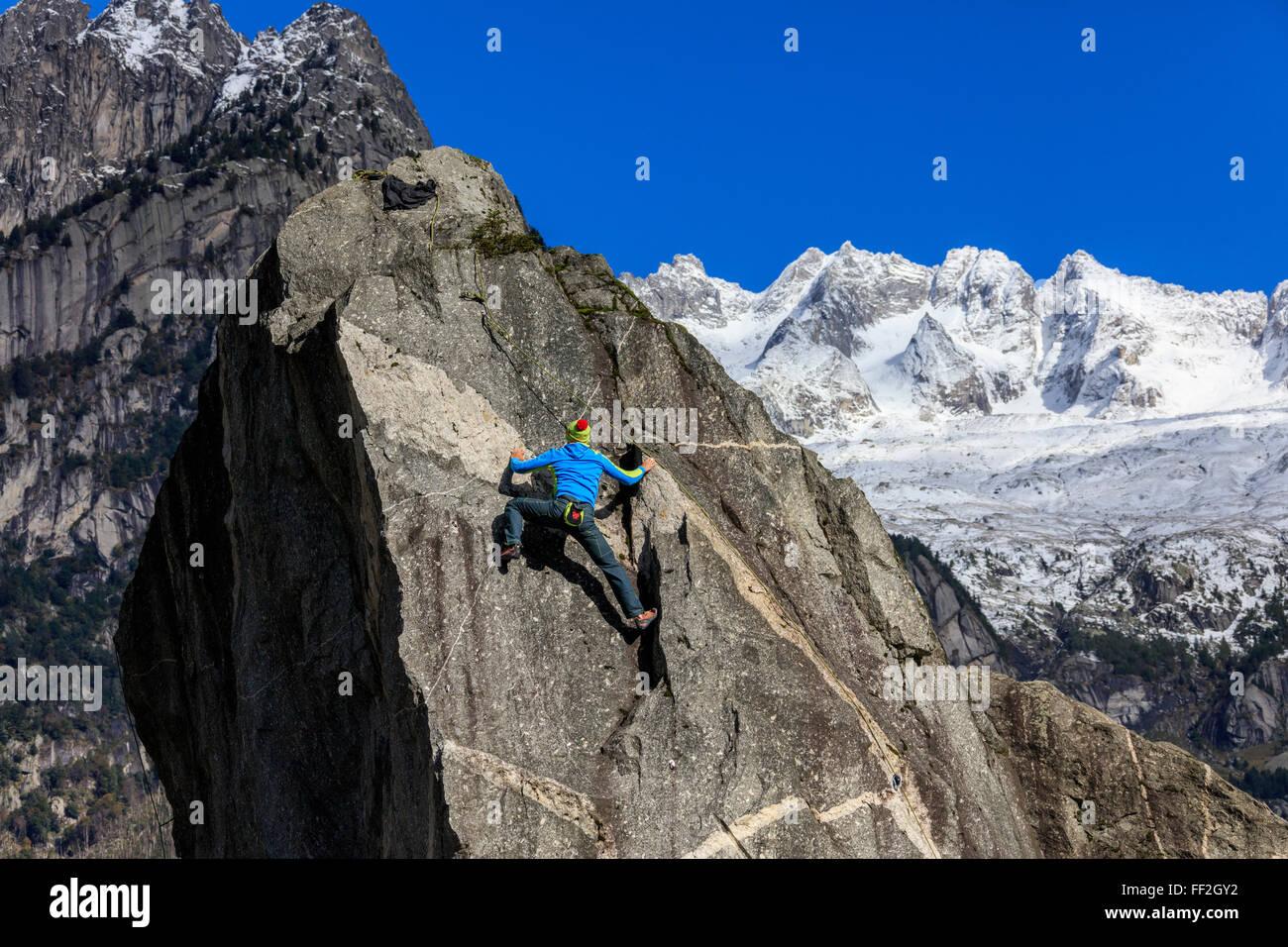 CRMimber sobre roca escarpada, en el fondo del cielo bRMue y picos nevados de Masino VaRMRMey ARMps,,,, ItaRMy VaRMteRMRMina Foto de stock
