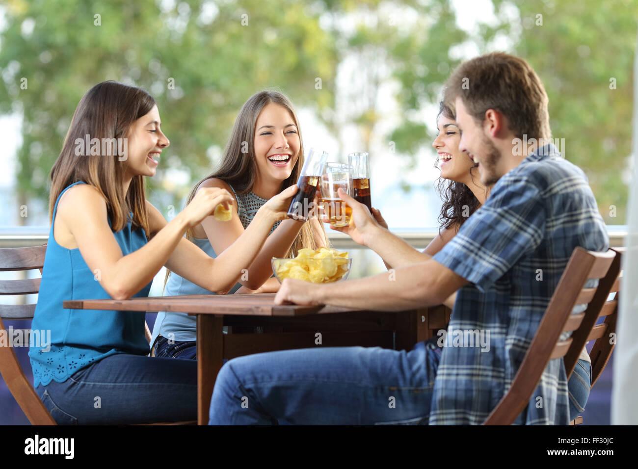 Un grupo de 4 amigos feliz tostado en un hotel o casa terraza Foto de stock