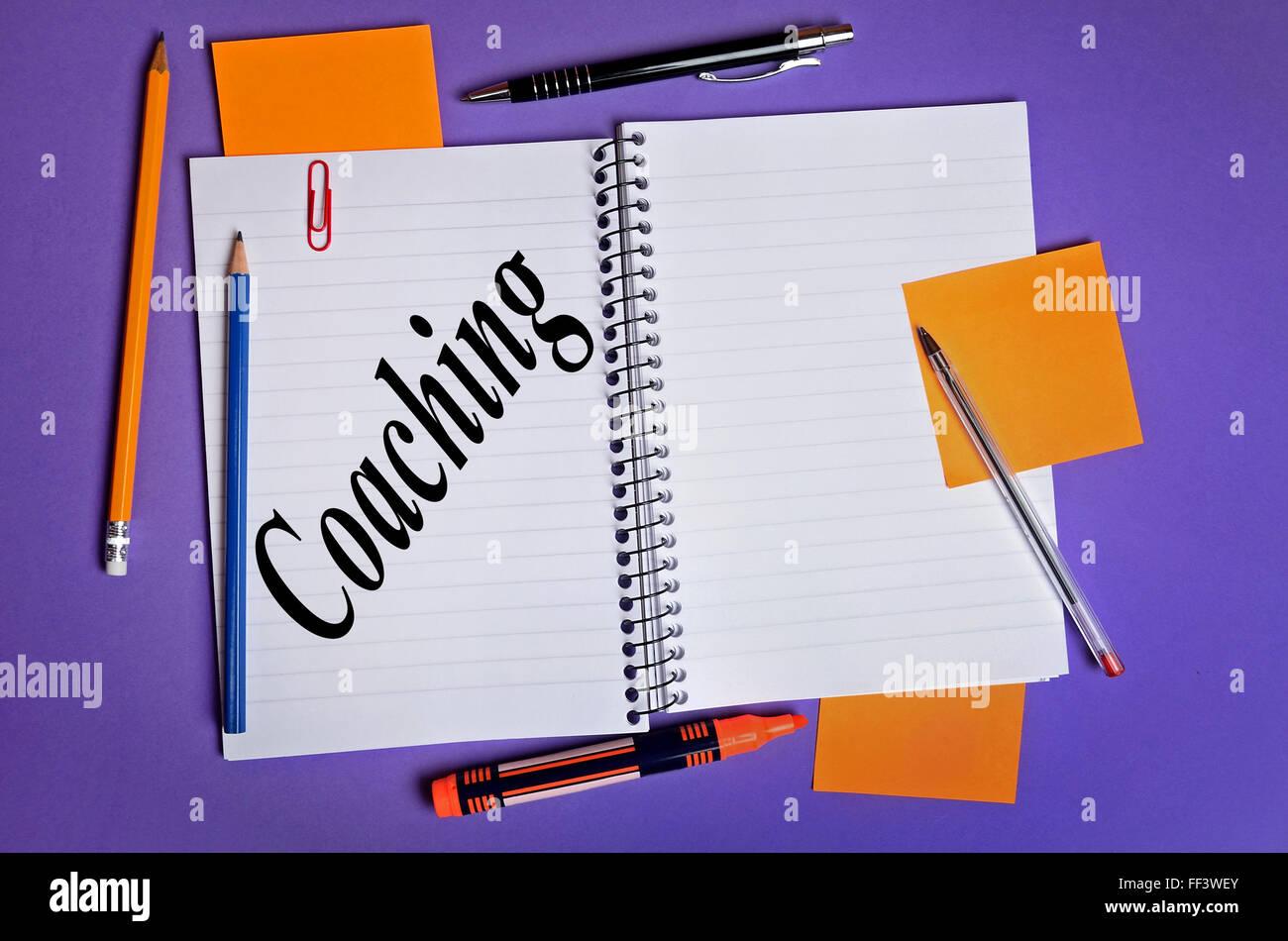 Coaching palabra escrita en el bloc de notas Imagen De Stock