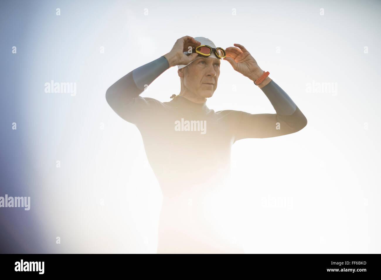 Un nadador en un traje y sombrero de natación, ajustando sus gafas de natación. Imagen De Stock