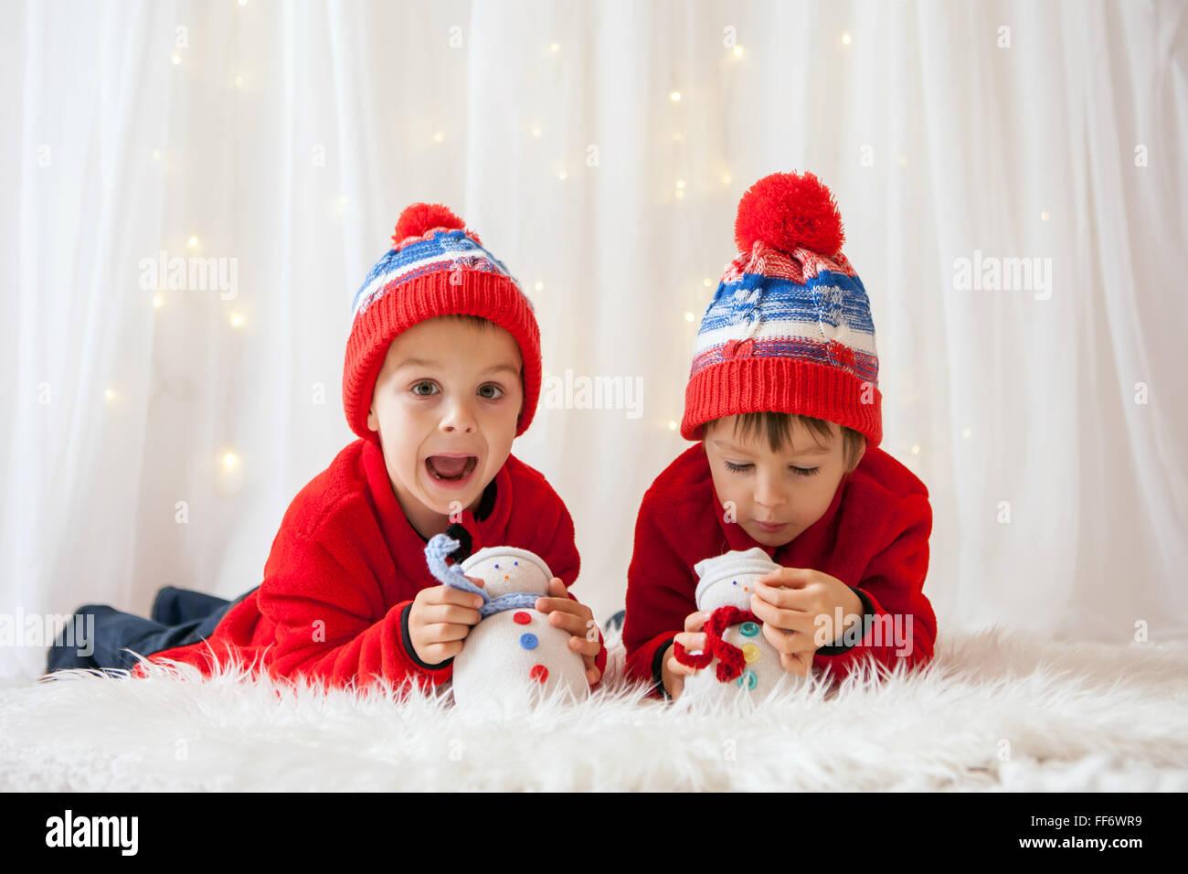 Sweet Children, hermano chicos, jugando con los muñecos de nieve artesanal en casa, las luces de Navidad detrás Imagen De Stock