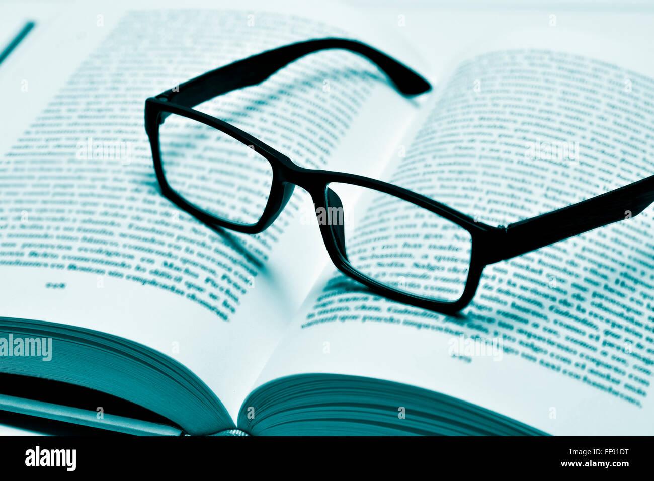 Primer plano de un par de lentes de montura de plástico negro sobre un libro abierto, en duotono Imagen De Stock