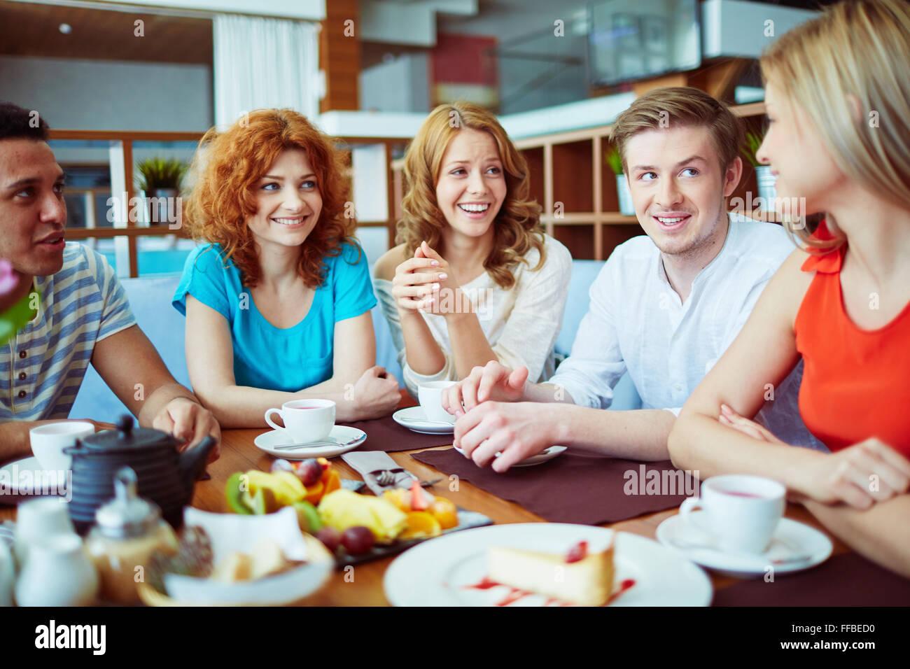 Tener amigos adolescentes hablar mientras está sentado en la cafetería Imagen De Stock