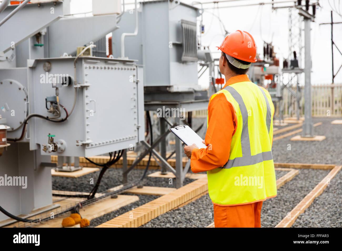 Vista posterior de la empresa de electricidad de trabajador de subestación Imagen De Stock