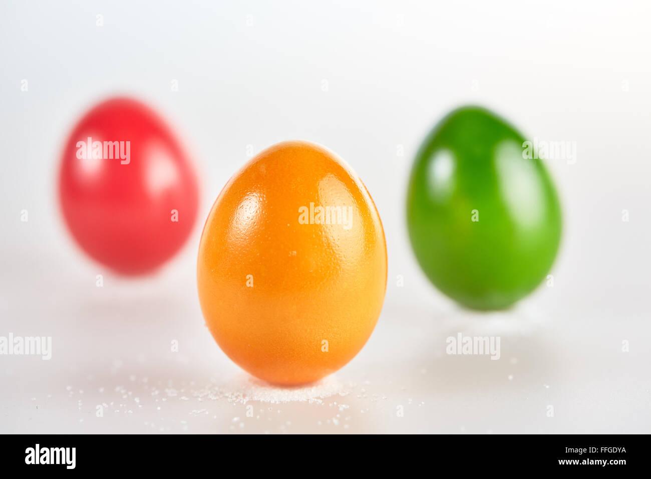 Tres huevos de pascua de color aislado de pie en pequeños montones de sal sobre fondo blanco. Imagen De Stock