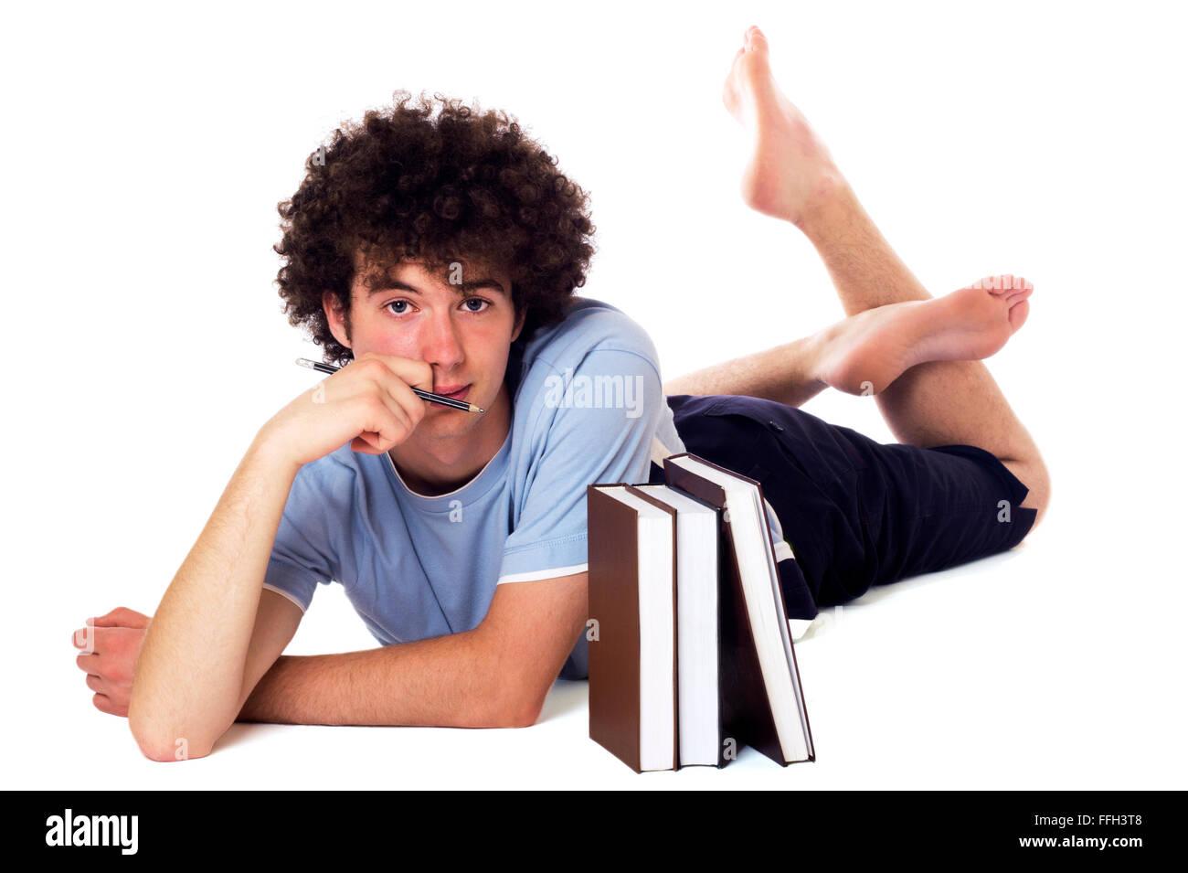 Pensativo adolescente con libros tumbado en el suelo y ha abatido la apariencia. Aislado en blanco. Imagen De Stock