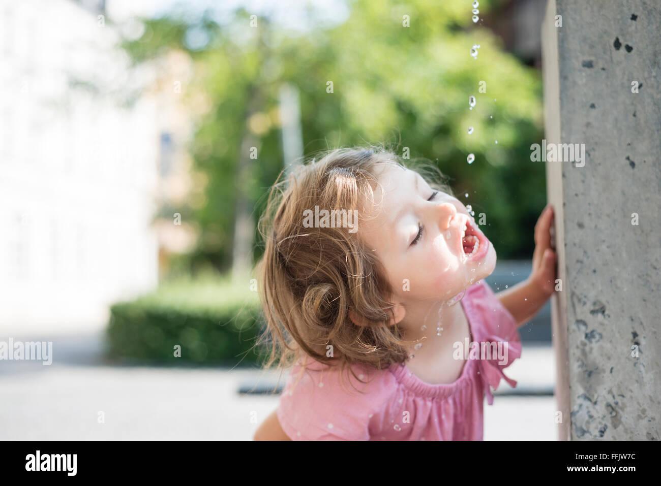 Niña de beber agua de la fuente Imagen De Stock