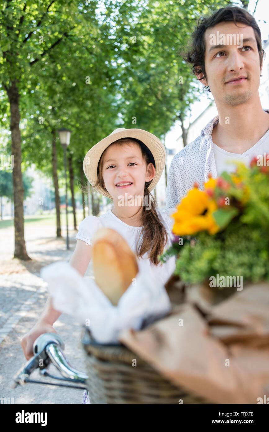 El padre y la hija con bicicleta y flores. Foto de stock