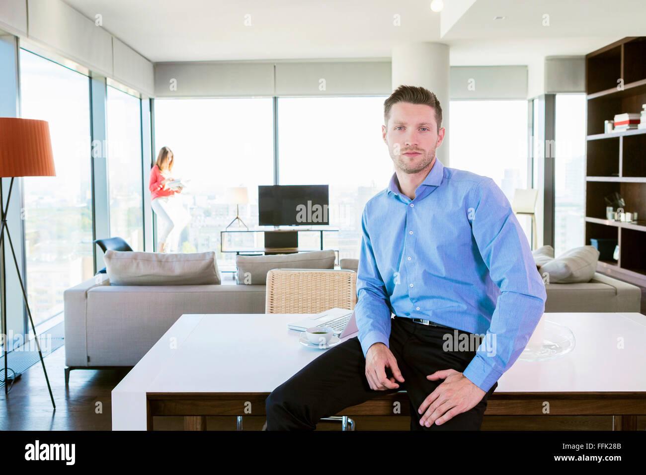 Hombre con actitud fresca en el apartamento con la mujer en segundo plano. Imagen De Stock
