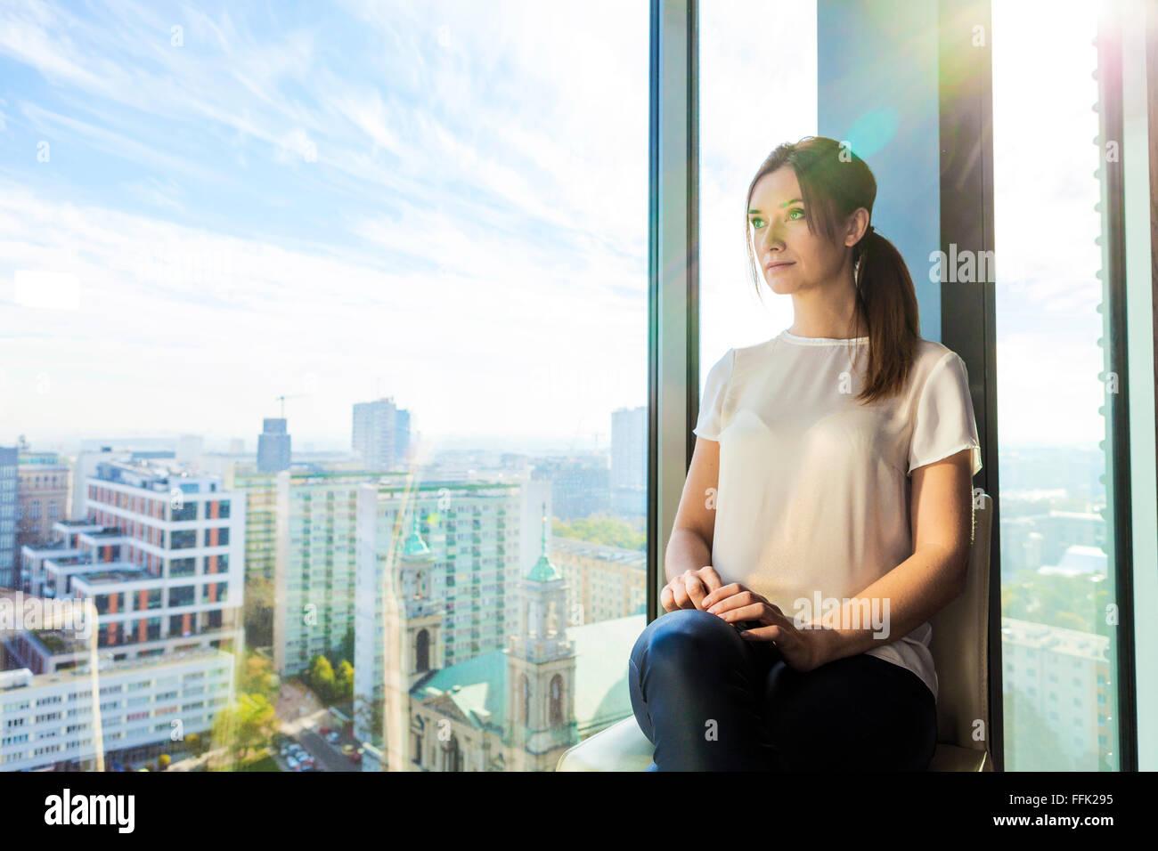 Mujer en el apartamento mirando a través de la ventana Foto de stock