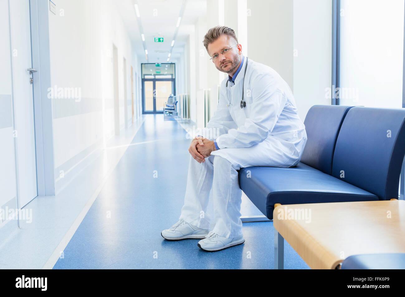 Médico toma un descanso sentado en el corredor del hospital Imagen De Stock