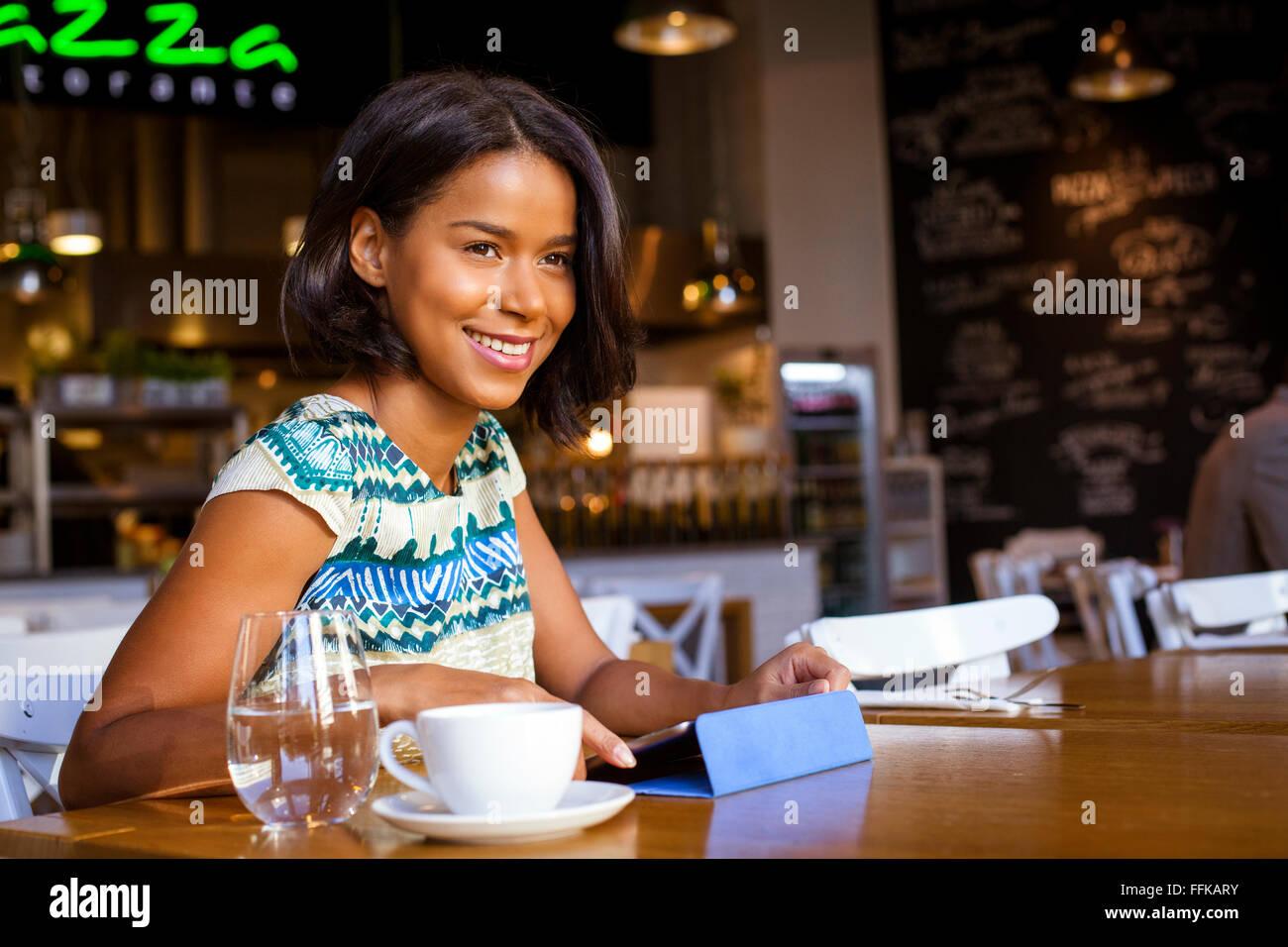 Raza mixta mujer sentada en el café utilizando el ordenador Imagen De Stock