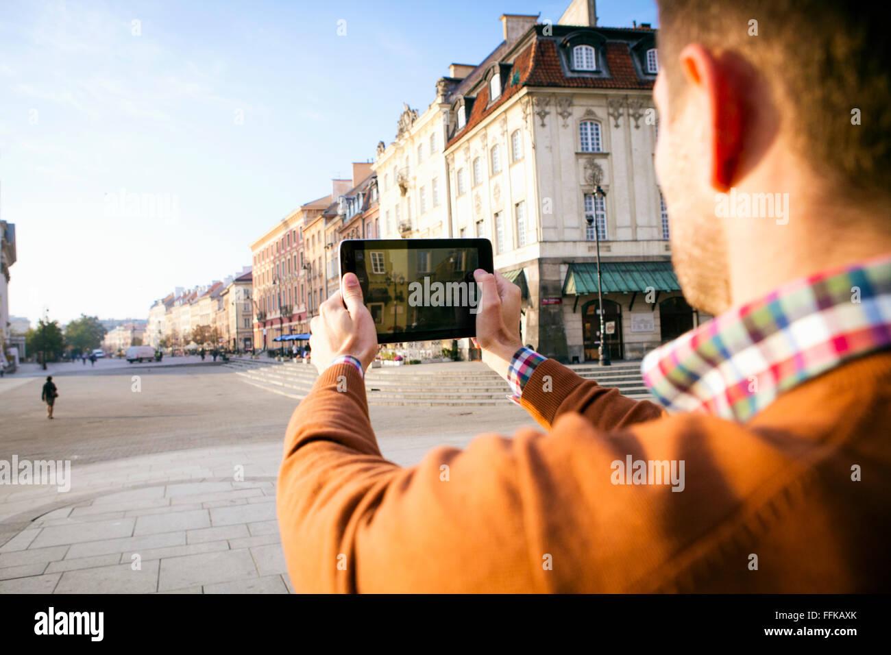 Hombre en una escapada a la ciudad tomando una fotografía con un teléfono inteligente. Foto de stock